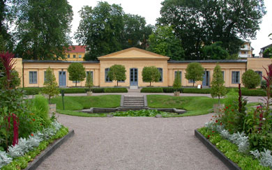 Photo of the Orangery, Hybernaculum, in The Linnaeus Garden, Uppsala University. There are eight trees clipped into ornamental shapes in front of the yellow buildning