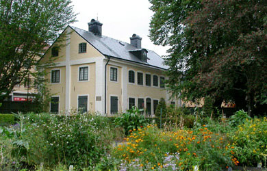 Photo of The Director's Lodge, in The Linnaeus Garden, Uppsala University. The hpus is built of stone and has a bright yellow plaster and green window frames. In front of the building the annual parterre is in full bloom.