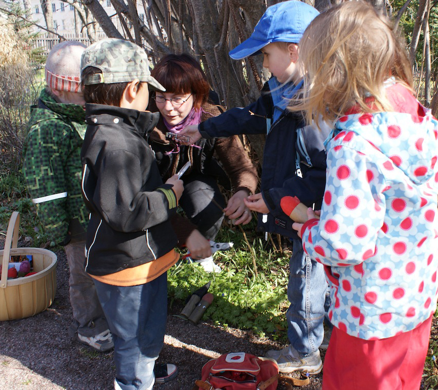 The botanist shows some plants to a group of children.