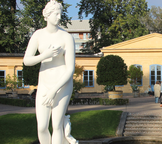 Photo of the white-painted statue Venus Medici in front of the Orangery in The Linnaeus Garden.